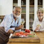 料理を作る男性とワイングラスを持つ女性