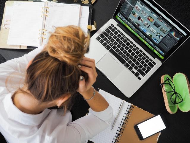 パソコンを見てお金が貯まらないと悩む女性
