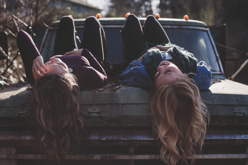 車のボンネットに横たわる二人の女性