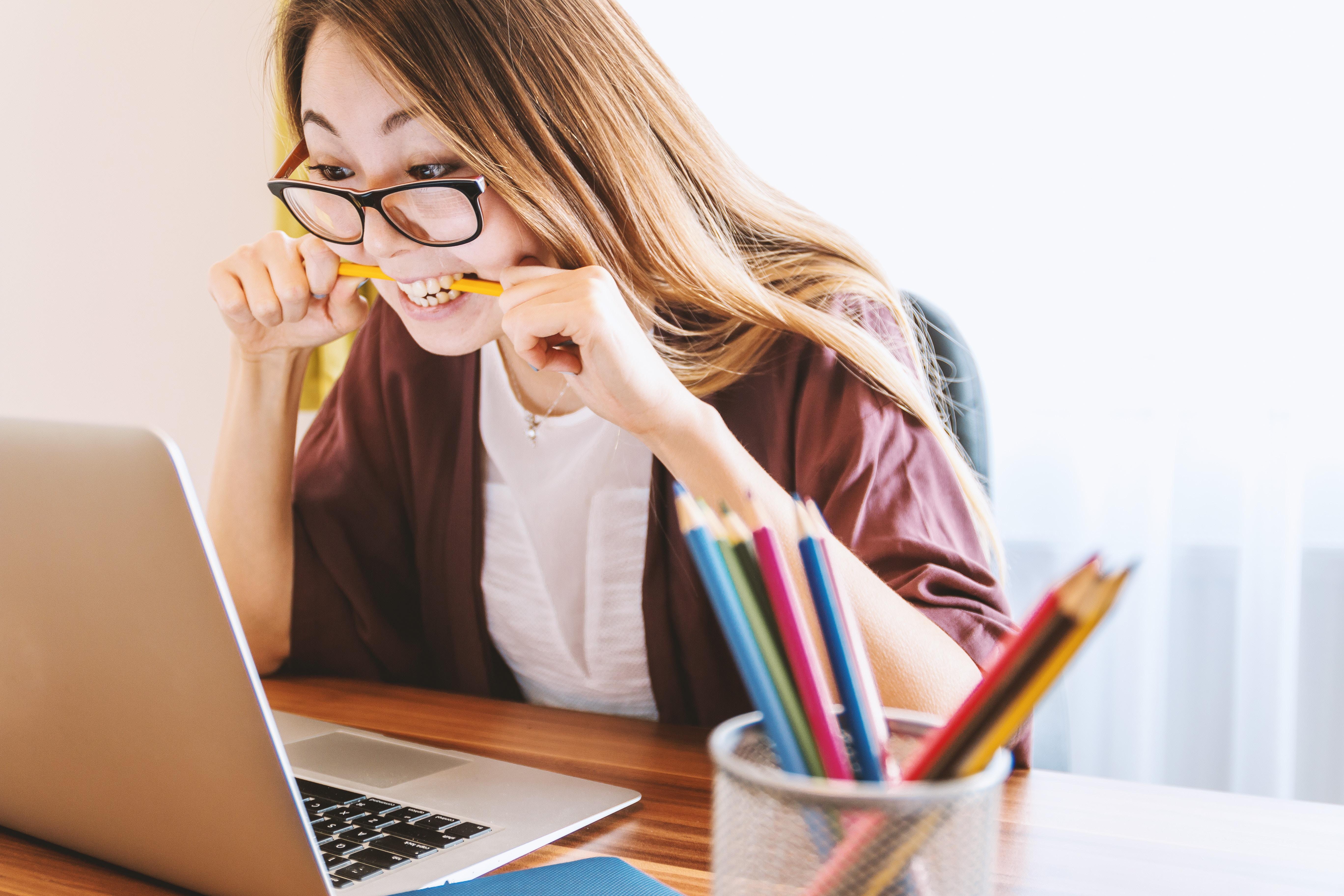 パソコンの前で鉛筆を噛む女性