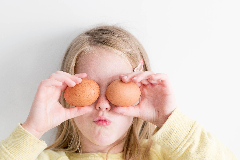 卵を両目にあてる女の子