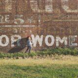 FOR WOMENと書かれた壁の前に立つ女の子