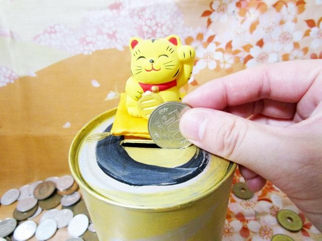 猫の貯金箱にお金を入れる