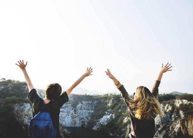 山頂で手を広げて喜ぶ男女