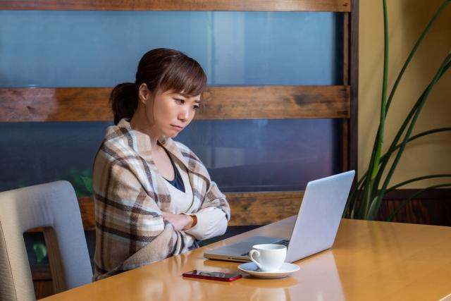 パソコンを険しく見つめる女性
