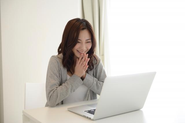 パソコンを見て喜ぶ女性