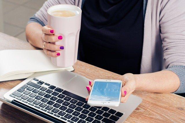 スマホとコーヒーを持つ女性