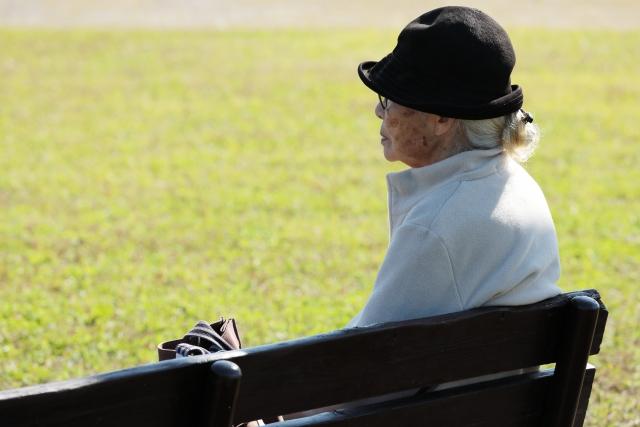 公園のベンチに座る老婆