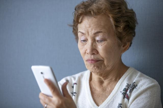 スマホを見る一人暮らしの高齢女性