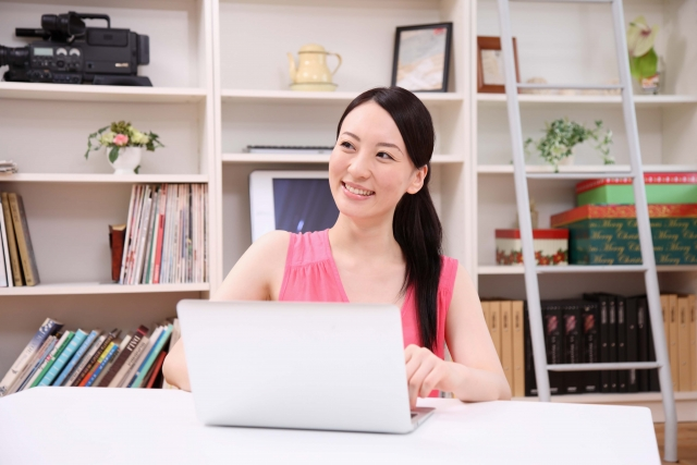 パソコンを操作する笑顔の女性