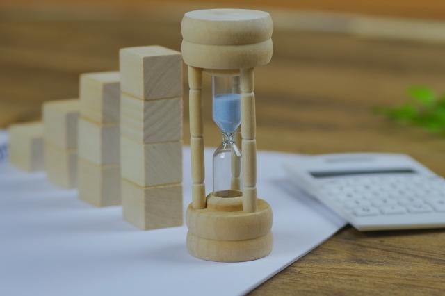 積み重ねるブロックと砂時計と電卓