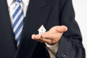 家の模型を持つビジネスマン