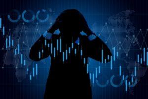 株式に悩む男性のシルエット