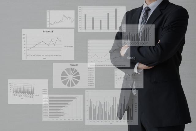 スーツ姿の男性と様々なグラフ