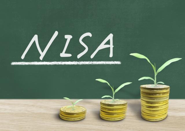 NISAと書かれた黒板と、積み立てたコインから出た芽