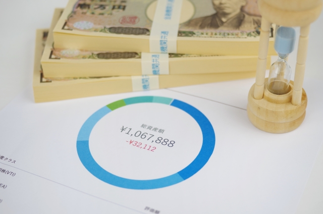 1万円の札束と総資産額が書かれた書類と砂時計