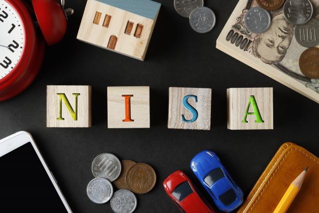 NISAと書かれたブロックとお金と文房具と時計と家や車の模型