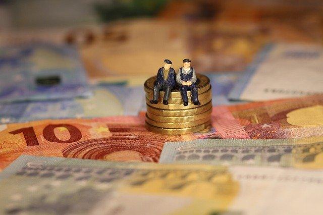 札束と積み上げられたコインに座る人形