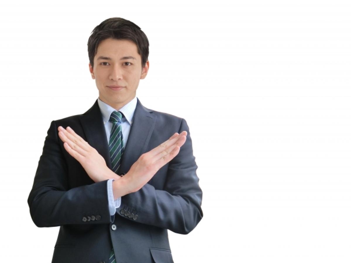 バツと手で示す男性の画像
