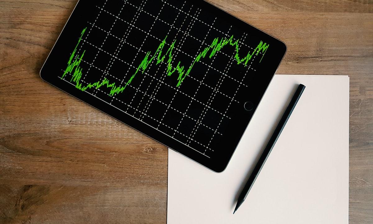 株のチャートを示すモバイルとペンのイメージ